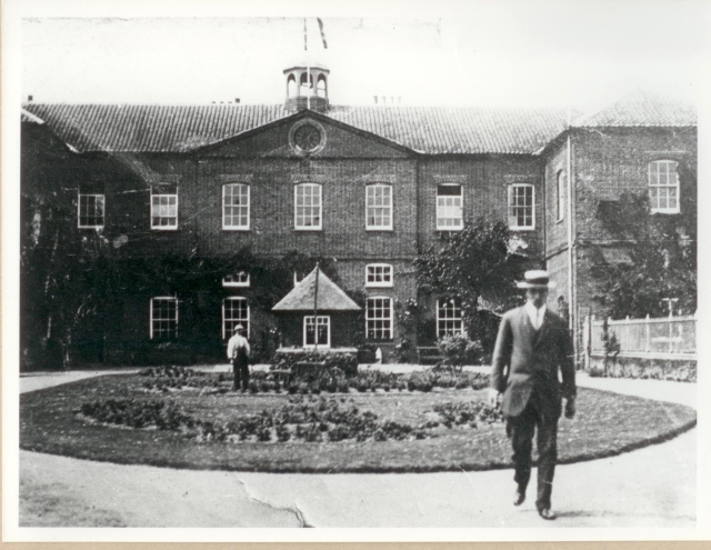 The entrance to the workhouse as it looked in the early 1900's - the well house stands next to the person to the rear