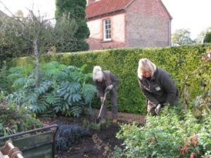Gardeners Jenny and Janet digging over and mulching the 'Red Border'