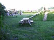 Oakes FF- picnic bench, slide and swings in older children's area