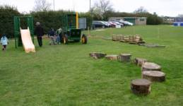 Toddler area with tractor, rrefurbished slide and log slice stepping stones