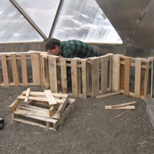 Cut down pallets being used in construction of a raised bed inside one of 'Growing Spaces' greenhouses