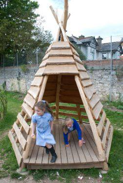 A play teepee made out of natural wood and recycled pallets