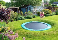 Some play equipment can be concealed or made into interesting garden features, like this sunken trampoline in a grass mound