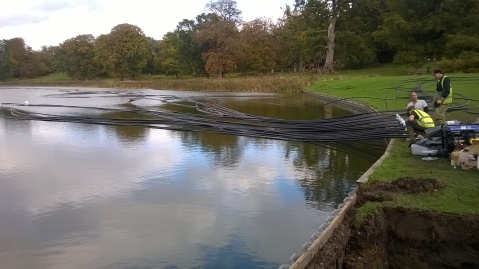 Plastic pipes being floated onto the lake- soon to be sunk and generating heat...