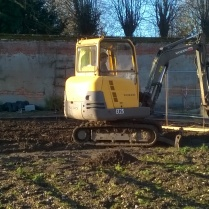 'Dud' at work with his digger, scraping back the top of the soil in the top beds; several lumps of concrete appeared...